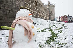 Windsor, UK. 24 January, 2021. A snowman stands in front of the walls of Windsor Castle following the first snowfall of winter. A spell of cold weather is expected to continue until Wednesday.