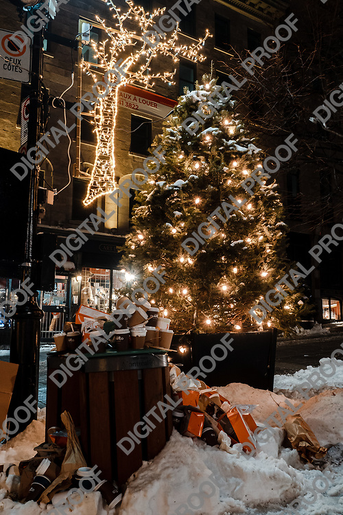 Montreal, Quebec, Canada - January 3, 2021 Public Garbage and waste cans overflown with drinks with plastics lids and snow close to Christmas lights and decorations