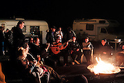 """A Gitan guitarist in Ricao Balliardo's camping site, plays flamenco around the fire. Saintes Maries festival<br /><br />""""Le Pelerinage des Gitans""""; the French gypsy pilgrimage of Saintes Maries de la Mer, Camargue, France<br /><br />Sainte Sara is an uncannonized saint, who legend says looked after the Christian Saints Marie Jacobe and Marie Salome, cousins of Mary Magdalene, who arrived, it is said, on the shores of the Camargue in a rudderless boat. Saint Sara is the patron saint of gypsies who come from far and wide to see her. There are even paintings of Sara as 'Kali' the black saint in Eastern Europe. Sara may have been the priestess of 'Ra' the sun-god or even servant girl to the Christian saints. No-one really knows.<br /><br />For a few weeks of the year, Roma, Gitan and Manouche gypsies come from all over Europe in May, camping in caravans around Saintes Maries de la Mer. It is a festive time where they play music, dance, party and christen their children. They all go to see Saint Sara in the crypt, kissing or touching her forehead. Many put robes on her shoulders, making her fat for the procession. In the main Gypsy procession of the 24th May, Saint Sara is allowed to leave her crypt, beneath the church, and is carried from the church to the shores of the mediterranean and back again. One day a year she is free from her prison. Hundred's of years ago the Gypsies used not even to be allowed into the church, only into the crypt like Sara...<br /><br />Roma gypsies still suffer oppressive prejudice and racism and are one of the ethnic groups the most persecuted and marginalised across Europe. The festival is one of the times where they celebrate with people of all races, their faith and traditions"""