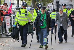 © Licensed to London News Pictures. 09/10/2019. London, UK. Police detain DAVID (who has five great grand children) and JOHN, aged 91(at the back) outside Cabinet Office in Westminster on day three of the two weeks protest by environmental and climate change activists. The activists are calling for the government to act on climate change. Photo credit: Dinendra Haria/LNP
