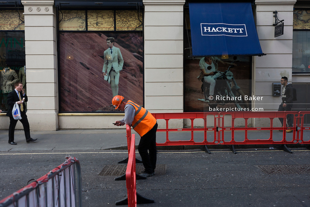 Construction worker outside the mens' clothing outfitters Hackett in Philpot Lane in London's Square Mile.
