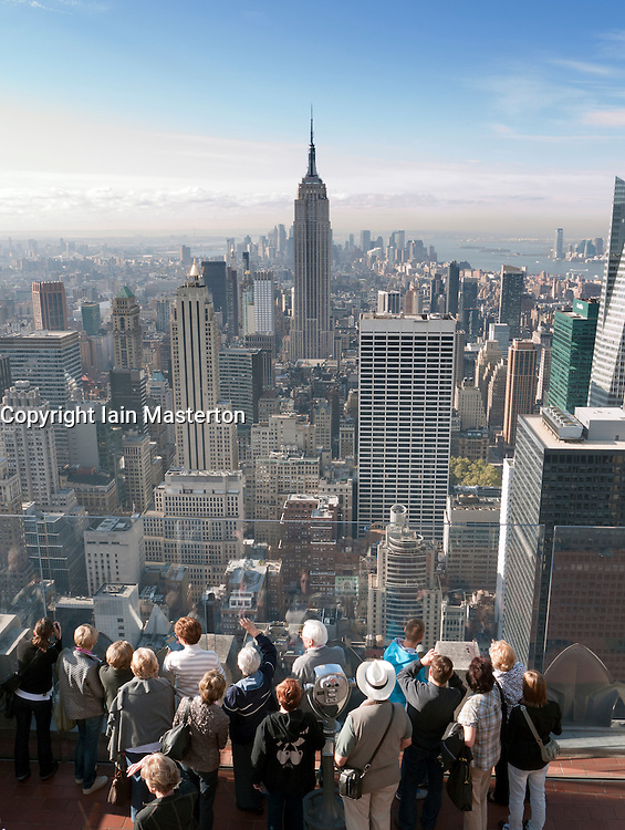 Tourists looking at Empire State Building from Top of The Rock observation platform  at Rockefeller Center in Manhattan New York city