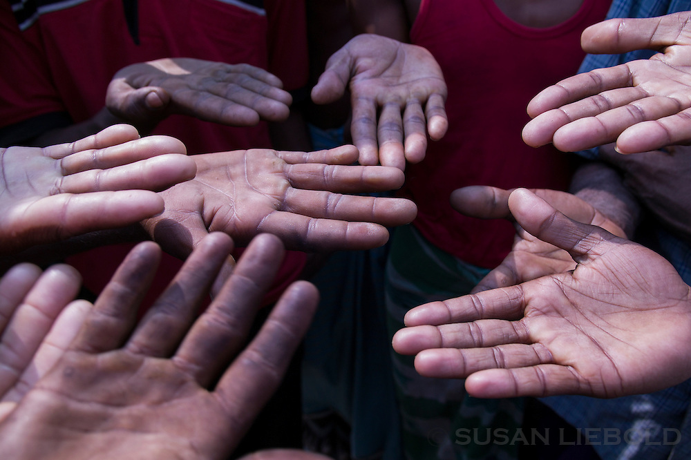 Men at a brick making factory in Bangladesh compare hands for callouses.
