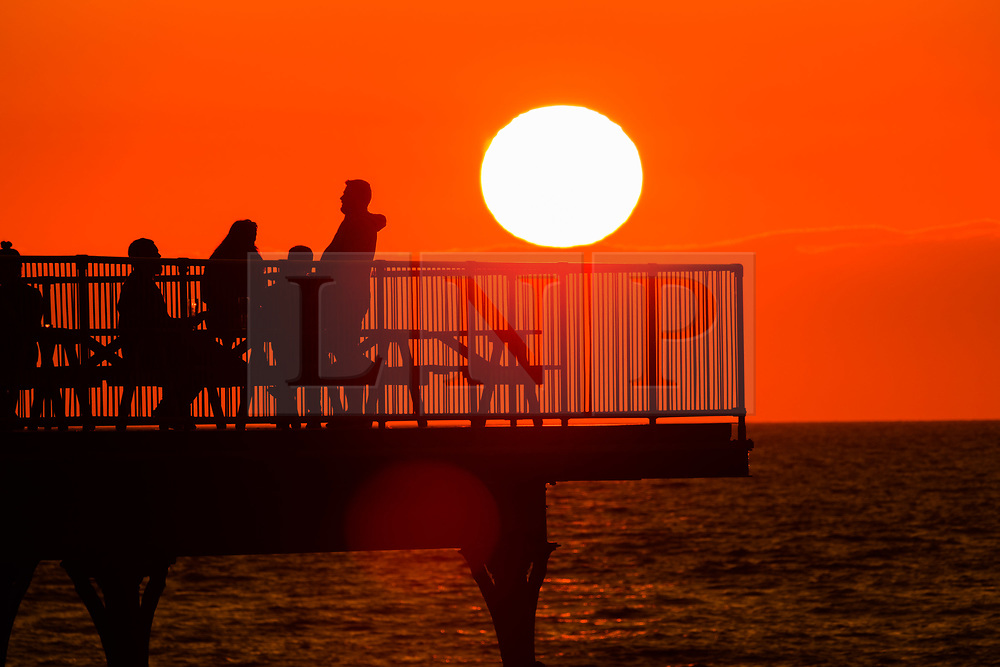 © Licenced to London News Pictures<br /> 20/05/2019. Aberystwyth, UK. People enjoying the glorious golden sunset over Cardigan Bay, at the end of a day of warm spring sunshine in Aberystwyth Wales. The weather is set fine for the coming days , with extended spells of warm sunshine. Photo credit: Keith Morris/LNP