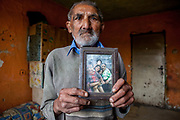"""Jan Ondic - 87 years of age (2014) - is one of the oldest inhabitants at the Roma settlement. He is holding a frame with a photograph of his beloved wife - she passed away a long time ago and now he lives by his own, but with her in his memories. He lives at the Roma part of the district """"Podsadek"""". The town of Stara Lubovna has a population of 16350, of whom 2 060 (13%) are of Roma origin. The majority of Roma live in the Podsadek district, where 980 (74%) out of 1330 inhabitants are Roma."""
