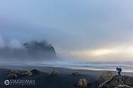 Photographer takes in mody scene at Vesterhorn Mountain near Hofn, Iceland