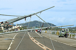 ALBAY, Dec. 26, 2016  Residents pass by electric poles that were toppled by strong winds from Typhoon Nock-Ten in Albay Province, the Philippines, Dec. 26, 2016. Typhoon Nock-Ten is battering provinces south of Manila, leaving at least three people dead, police and local officials said on Monday.  Authorized by ytfs* (Credit Image: © Stringer/Xinhua via ZUMA Wire)
