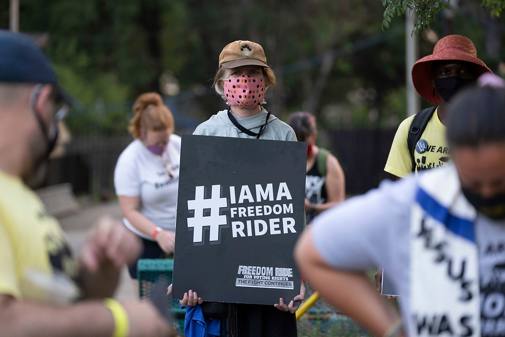CHRISTI VORNELL of Santa Cruz, CA, holds a sign as voting rights  groups march toward the Texas Capitol from north Austin on the third day of a 30-mile journey protesting Republican efforts to suppress votes nationwide and in Texas. Shifts of marchers trade off in an effort to combat oppressive Texas heat.