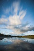 Long exposure shows speedy cloud trails over lake at full moon night, Purezers Lake nature trail, Latvia Ⓒ Davis Ulands | davisulands.com