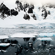"""Scenic mountains covered in snow and ice lining the side of the Lemaire Channel on the western side of the Antarctic Peninsula. The Lemaire Channel is sometimes referred to as """"Kodak Gap"""" in a nod to its famously scenic views."""