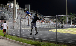 August 18, 2018 - Wellington, Florida, U.S. - Students scale a fence to escape from gunfire during the fourth quarter of a football game at Palm Beach Central high School. Two adults were shot Friday night at a football game between Palm Beach Central and William T. Dwyer high schools, authorities said. The gunfire sent players and fans screaming and stampeding in panic during the fourth quarter of the game at Palm Beach Central High School in Wellington, Florida on August 17, 2018. (Credit Image: © Allen Eyestone/The Palm Beach Post via ZUMA Wire)