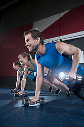 Athletes doing push ups in the gym by holding dumbbell, Bavaria, Germany