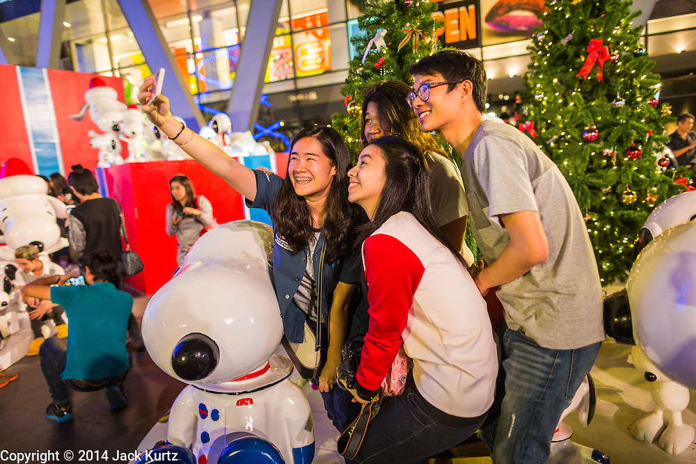 """17 DECEMBER 2014 - BANGKOK, THAILAND: People pose for """"selfies"""" among the Christmas trees in front of Central World in Bangkok. Thailand is overwhelmingly Buddhist. Christmas is not a legal holiday in Thailand, but Christmas has become an important commercial holiday in Thailand, especially in Bangkok and communities with a large expatriate population.    PHOTO BY JACK KURTZ"""
