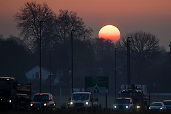 © Licensed to London News Pictures. 18/04/2021. London, UK. Traffic builds during sunrise on Blackheath Common in South East London. Temperatures are expected to rise with highs of 17 degrees forecasted for parts of London and South East England today . Photo credit: George Cracknell Wright/LNP