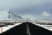 A clear road crosses the western tip of the Snaefellsnes Peninsular in Western Iceland