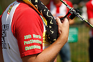 Photo by Andrew Tobin/Tobinators Ltd - 07710 761829 - Jim Collin's t-shirt and snake-themed peashooter during the World Peashooting Championships held at Witcham, Cambridgeshire, UK on 13th July 2013. Run in conjunction with the village fair, the Championships have been held in Witcham since 1971 when they were started by a Mr Tyson, the village schoolmaster, in order to raise funds for the village hall.Competitors come from as far afield as the USA and New Zealand to attempt to win the event. The latest technology is often used, including laser sights and titanium and carbon fibre peashooters. All peashooters must conform to strict length rules, not exceeding 12 inches, and have to hit a target 12 feet away. Shooting 5 peas at a plasticine target attached to a hay bale, the highest scorers move through the initial rounds to a knockout competition, followed by a sudden death 10-pea shootout.