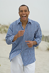 man on the beach laughing while walking