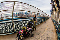 A Muslim woman pushing a baby carriage across the Manhattan Bridge (with Lower Manhattan in background), New York City, NY USA.