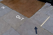 A detail view of In and Out markings clearly marked out on the ground, at the entrance and exit of a corporate address during the third lockdown of the Coronavirus  pandemic, in the City of London, the capitals financial district, on 10th February 2021, in London, England.