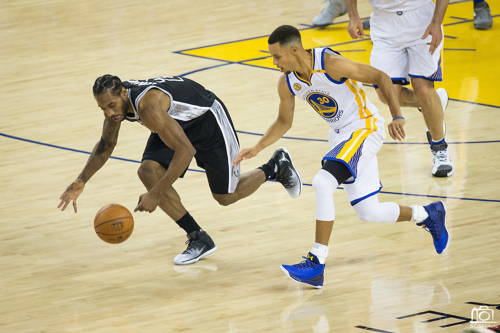Golden State Warriors guard Stephen Curry (30) and San Antonio Spurs forward Kawhi Leonard (2) race for a loose ball during the NBA season opener at Oracle Arena in Oakland, Calif., on October 25, 2016. (Stan Olszewski/Special to S.F. Examiner)