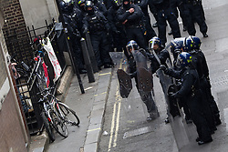 "© Licensed to London News Pictures . 11/06/2013 . London , UK . Police with full length riot shield stand outside the entrance as police surround a former police station on 40 Beak Street , Soho this morning (11th June) which has been occupied by organisers as a base for today's "" Stop G8 "" anti capitalist protest . Demonstrations in London today (Tuesday 11th June 2013) ahead of Britain hosting the 39th G8 summit on 17th/18th June at the Lough Erne Resort , County Fermanagh , Northern Ireland , next week . Photo credit : Joel Goodman/LNP"