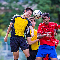 Players from Victoria Junior College (yellow) and Millenia Institute (red) challenge for the header during the group stage match of the National 'A' Division Football Championship at Nanyang Junior College on May 12, 2014, in Singapore.