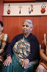 Elderly woman taking part in meditation section of exercise class,