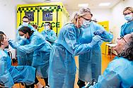 I kælderen under Herlev Hospital står en stor flok sundhedsmedarbejdere fra Region Hovedstaden. Iført værnemidler, blå kittel, gummihandsker og beskyttelsesbriller stikker de en podningspind ind i munden på hinanden indtil de fremkalder en lille opkastlyd.<br />  Grundet det høje smittetryk i København og omegn er der brug for stadig flere der kan foretage COVID-19 podningstest og uddannelsen foregår under kyndig vejledning fra sygeplejersken på Herlev Hospital.