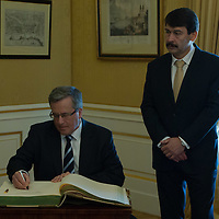 Janos Ader (R) president of Hungary watches as Bronislaw Komorowski (L) president of Poland signs the guest book after a welcoming ceremony in Budapest, Hungary on March 21, 2014. ATTILA VOLGYI