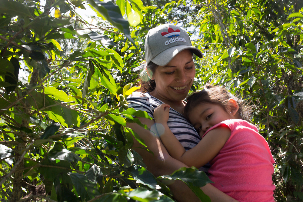 Olga Alvarado, coffee producer with COAQUIL Coop in Quiragüira, Intibucá, Honduras, pictured here with her daughter Genesis. Olga migrated to the US for eight years, working in McDonalds and Wendy's burger joints to save up enough to buy a small plot of land in Honduras and return to grow coffee.