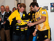 Hurricanes captain Conrad Smith presents Prince Harry with a personalised onesie for his brother's daughter, Princess Charlotte, in the Hurricanes changing rooms after the Super Rugby match between the Hurricanes and Sharks at Westpac Stadium, Wellington, New Zealand on Saturday, 9 May 2015. Photo: Dave Lintott / POOL PHOTO