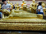 31 MAY 2017 - CHACHOENGSAO, THAILAND: People apply gold leaf to a statue of the reclining Buddha at Wat Sothon (also spelled Sothorn) in Chachoengsao, Thailand. The temple is one of the largest and most visited in Thailand. People make merit by paying to wrap the Buddha statues in yellow robes. The temple is most famous because people leave hard boiled eggs as an offering at the temple. They ask for business success or children and leave hundreds of hard boiled eggs.      PHOTO BY JACK KURTZ