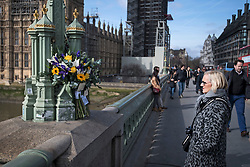 © Licensed to London News Pictures. 22/03/2018. London, UK. Members of the public look at floral Tributes left by family of the deceased at Westminster Bridge in London on the one year anniversary of the Westminster Bridge Terror attack in which lone terrorist killed 5 people and injured several more, in an attack using a car and a knife. The attacker, 52-year-old Briton Khalid Masood, managed to gain entry to the grounds of the Houses of Parliament and killed police officer Keith Palmer. Photo credit: Ben Cawthra/LNP