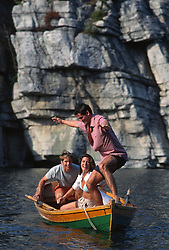 Three friends playing in a rowboat