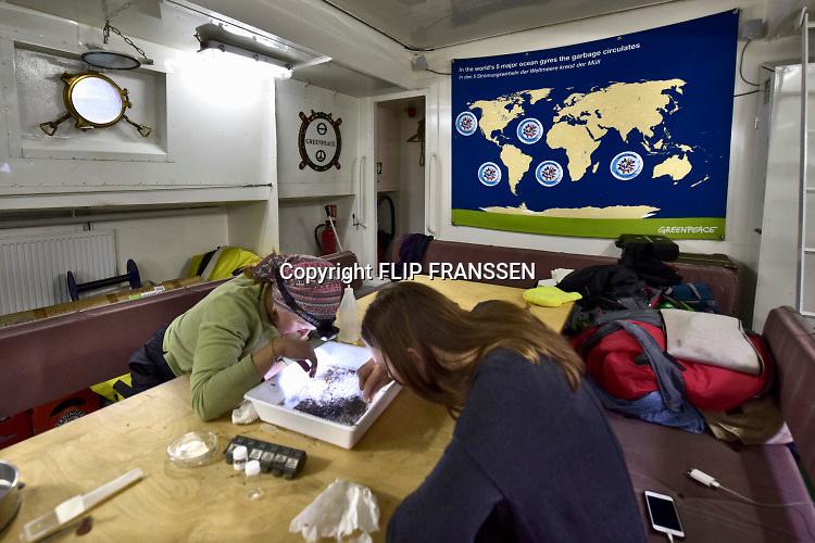 Duitsland, Germany, Keulen, 28-3-2019Twee schepen van Greenpeace, de Beluga 2 en een gehuurd binnenvaartschip zijn aangekomen in Keulen op weg naar Basel om met het PlasticMonster aandacht te vragen en te protesteren tegen het plastic in de rivieren, met name in de Rijn. Hun actie richt zich ook op fabrikanten Nestle en Unileverom geen wegwerpplastic meer te gebruiken als verpakkingsmateriaal voor hun producten.De Plasic Monster Ship Tour . Op het Greenpeace actieschip De Beluga II is een geimproviseerde labopstelling gemaakt om monsters van plastic deeltjes uit het rijnwater, rivierwater te halen. Grotere deeltjes worden met pincet en op het oog eruit gehaald, en met een pompje met een fijn filter de microdeeltjes. Ze worden in onderzoeksbuisjes en potjes gedaan om later uitgebreid onderzocht te worden op o.a. microben die zich eraan gehecht hebben waar o.a. dna onderzoek op kan worden gedaan.. No time te waste, plasticmonster, break free from plastic . De tocht begon in Nederland .Foto: Flip Franssen.