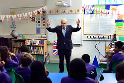 """© Licensed to London News Pictures. 23/04/2013. London, UK Mayor of London, Boris Johnson takes part in a Year 6 Class about St George's Day at Tidehall Academy in Deptford, South East London today 23rd April 2013. The class was taught by """"Outstanding Teacher"""" Ed Wickstead. During the lesson Mr jOhnson wore a """"sound field"""" device around his neck so his voice could be heard by the class. Photo credit : Stephen Simpson/LNP"""