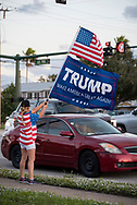 A young woman sticks out her tongue and gives the middle finger to a Trump supporter holding  a Trump 2020 flag on a sidewalk on election day, November 3, 2020, in Indialantic, Florida.