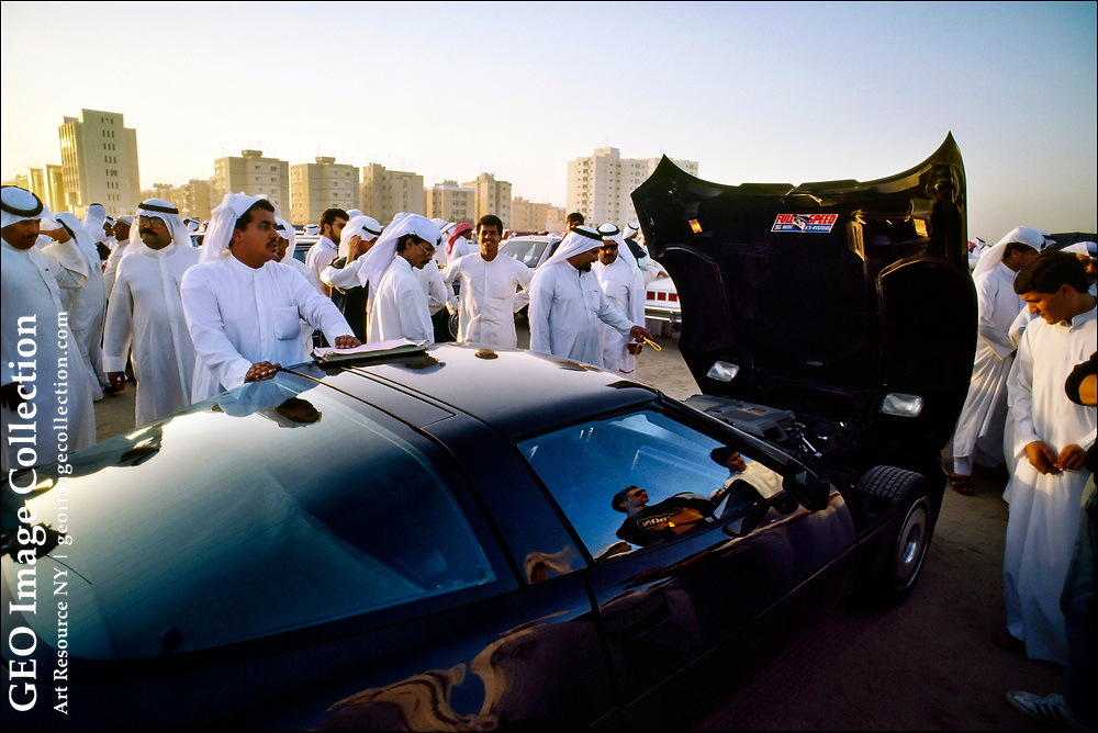"""Kuwaiti men, most wearing the traditional """"dishdasha,"""" or ankle-length white cotton shirt, inspect a Chevrolet Corvette at a daily auto auction in the desert at the edge of Kuwait city.  Kuwait is one of the richest countries in the world with an average salary running to $74,403 USD per year in 2021."""