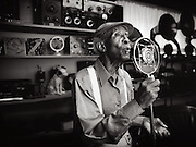 An elderly african-american man sings into a vintage microphone inside of a room full of antique radios.