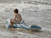 boy playing in the waves while sitting on a toy dolphin