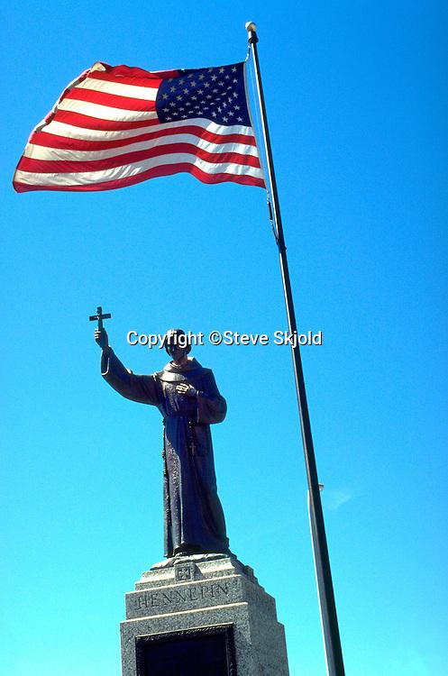 Statue of Saint Anthony holding cross below United States flag.  Minneapolis Minnesota USA