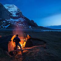 Two people enjoy campfire at Bunes Beach, Moskenesoy, Lofoten Islands, Norway