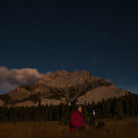 Sitting below the Big Dipper and Cascade Mountain, a photographer shoots moonlit scenes in Banff National Park, Alberta, Canada.