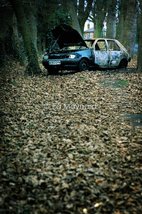 Burnt out, abandoned car on a country lane, Leicestershire, England.