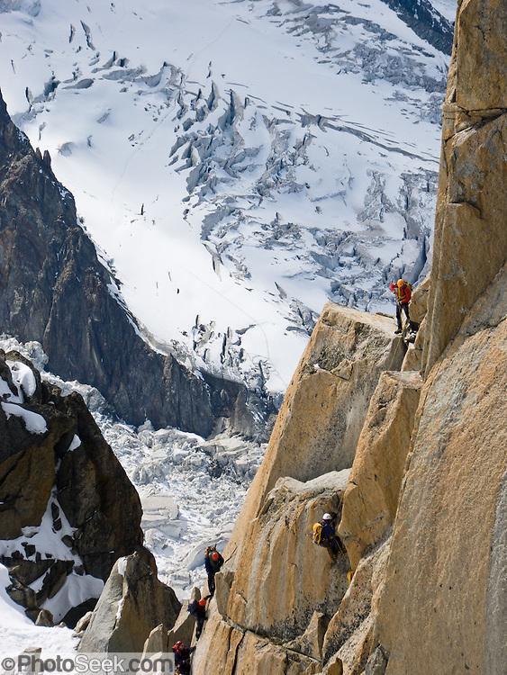 Rock climbers ascend Aiguille du Midi on Mont Blanc massif above a field of massive glaciers, Chamonix, France, Europe.