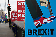 Placard depicting the UK shooting itself in the foot at the anti Brexit pro Europe demonstration in Westminster on 26th March 2019 in London, England, United Kingdom. With the date of the UK leaving the European Union extended, the pro EU protest continues as MPs from all sides try to gain control of the process.