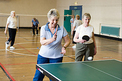 Group of elderly women playing table tennis and badminton in sports hall,