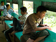 A man looks out of the window of a carriage on the Yangon Circular Railway, Myanmar (Burma). The railway, a narrow gauge local commuter rail network serving Yangon metropolitan area is a 28.5 mile (45.9 km) 39 station loop system. This British built rail-loop connects Yangon to its satellite towns and villages.