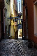 Narrow street, woman at end. Regensburg Germany