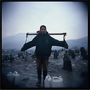 A boy carries water buckets in Kabul.
